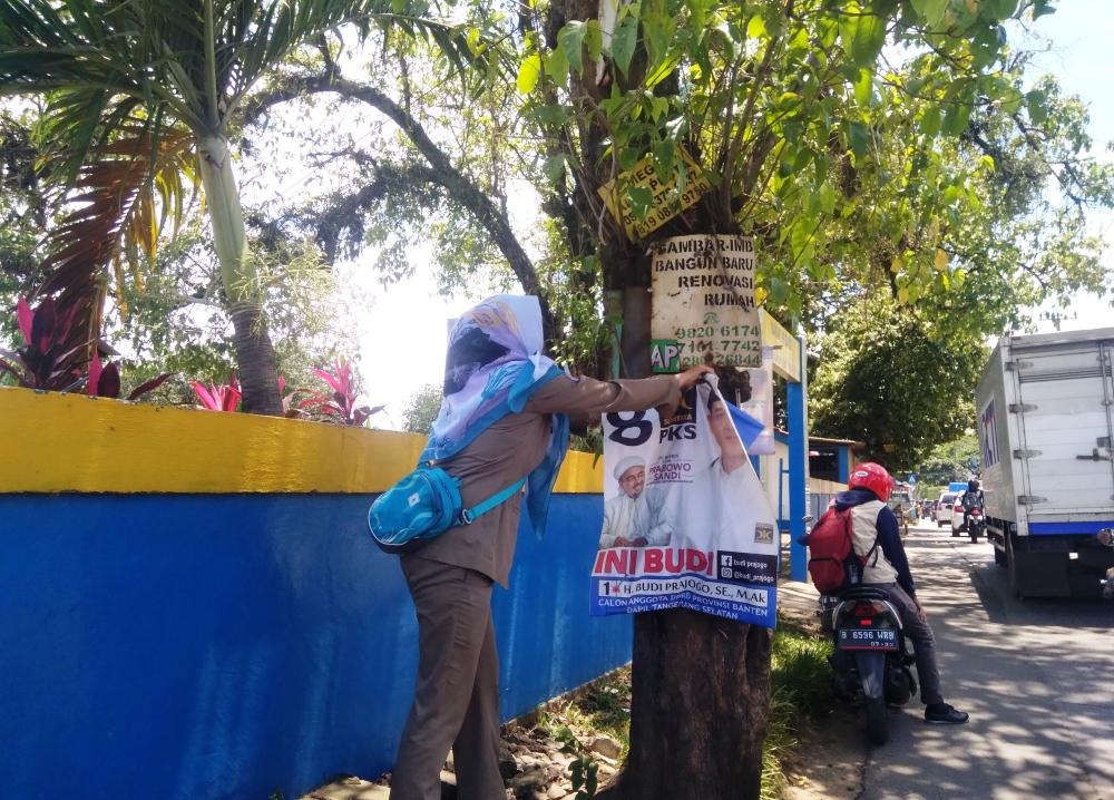 Petugas melakukan pencopotan alat peraga kampanye (APK) yang pemasangannya dinilai melanggar di wilayah Tangsel.