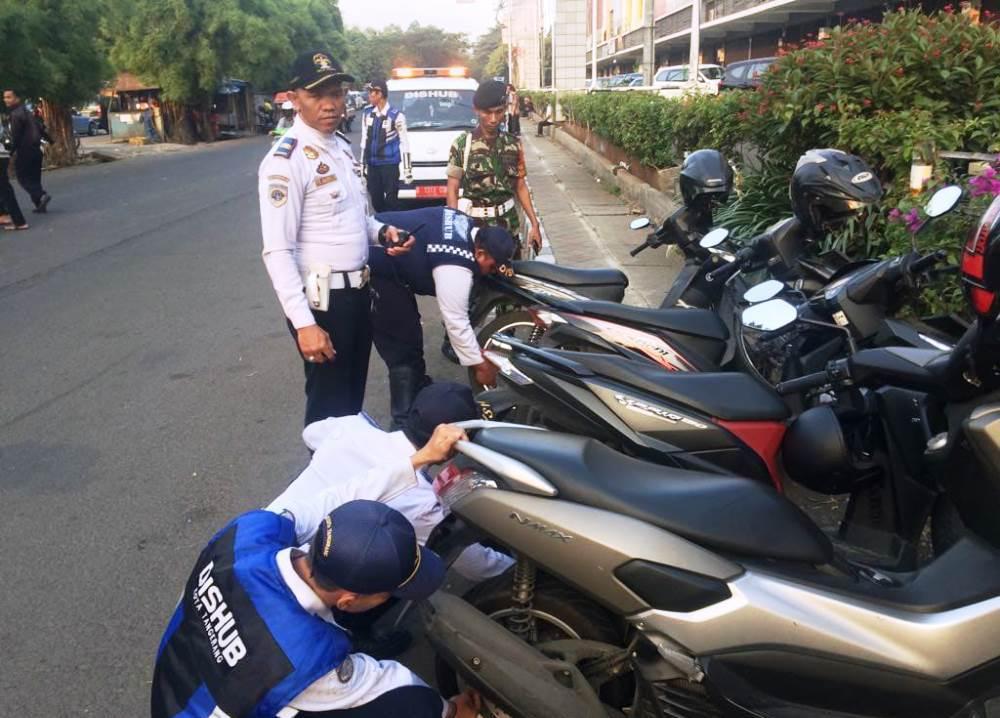 Petugas Dishub Kota Tangerang saat menertibkan pengendara roda dua yang parkir sembarangan di bahu jalan Kota Tangerang.
