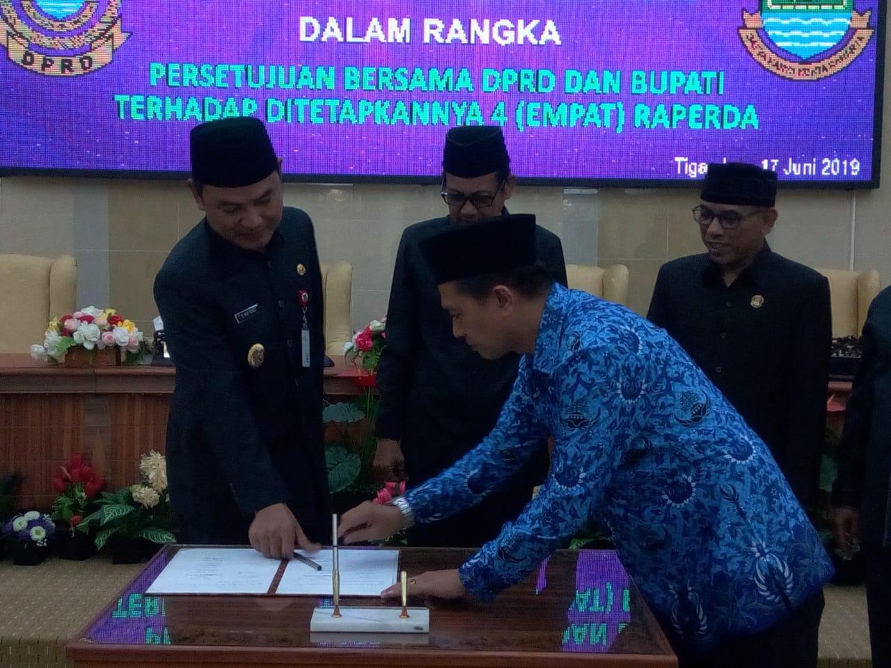 Ketua DPRD Kabupaten Tangerang, Sumardi saat menyerahkan dokumen Raperda kepada Wakil Bupati Tangerang, Mad Romli dalam Rapat Paripurna di Gedung DPRD Kabupaten Tangerang, Senin (17/6/2019).