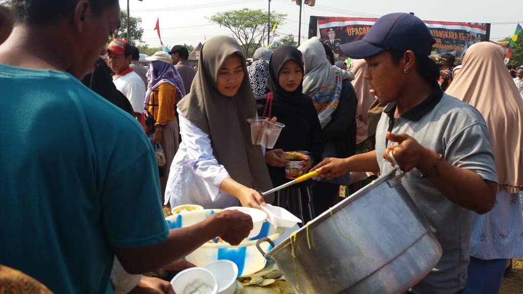 Suasana masyarakat yang ikut makan gratis pada Perayaan HUT Bhayangkara ke-73, di Lapangan Nunggul, Kelurahan Sukatani, Kecamatan Rajeg, Rabu (10/7/2019).