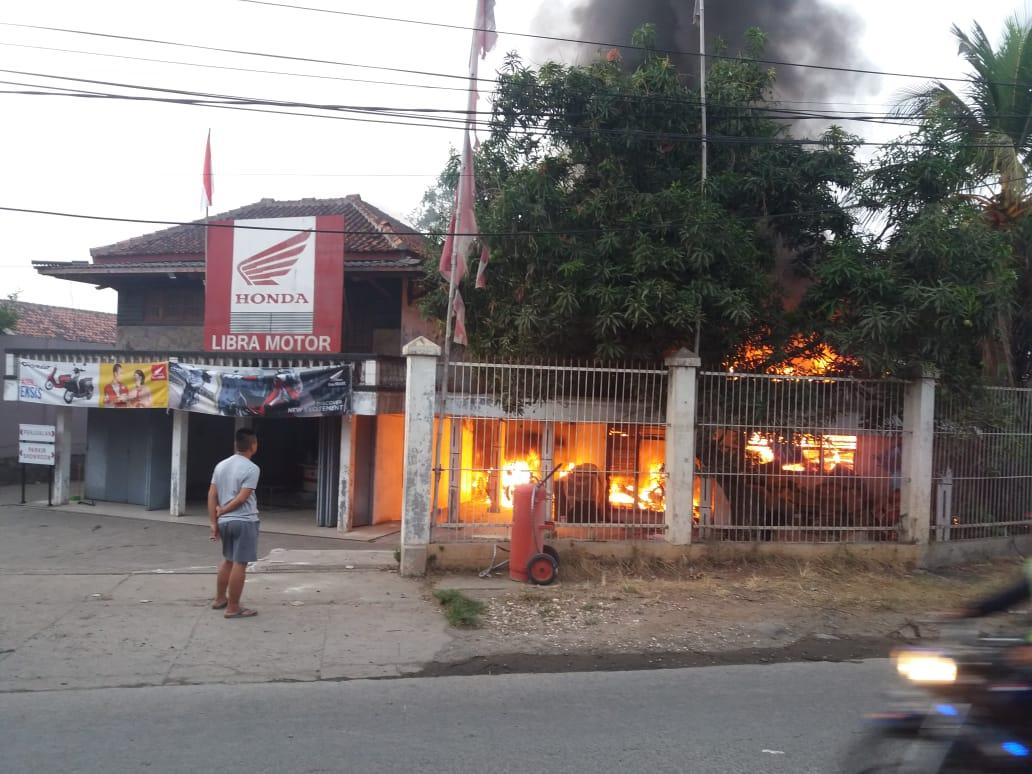 Tampak petugas pemadam kebakaran berusaha memadamkan api yang berkobar di showroom sepeda motor di Kampung Babakan Tengah, RT 01/02, Kelurahan Babakan, Kecamatan Legok, Kabupaten Tangerang.