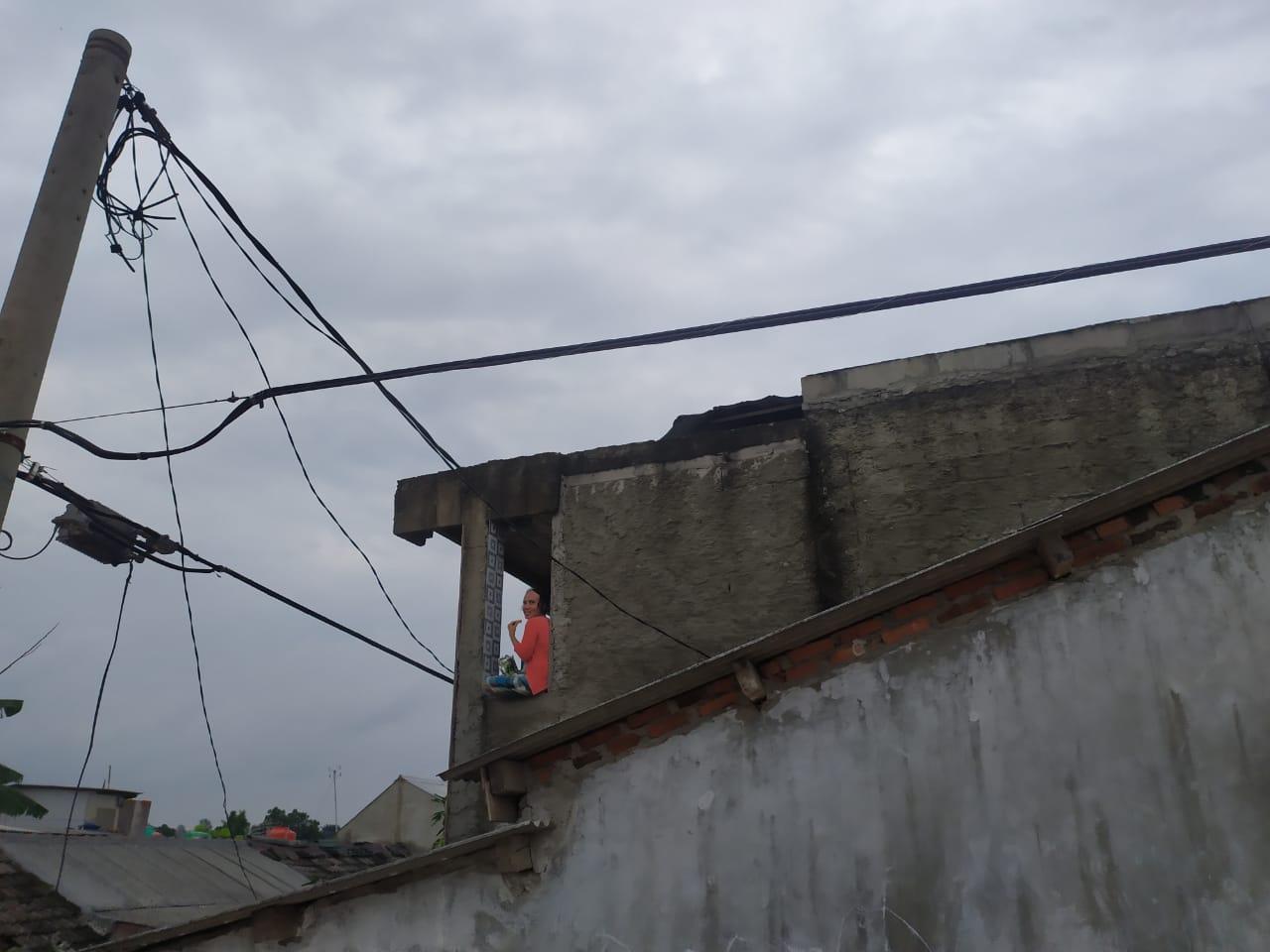 Tampak ibu-ibu bertahan di atap rumahnya padahal terdampak banjir di Perumahan Pesona Serpong, Kademangan, Setu, Tangsel, Rabu (1/1/2020).
