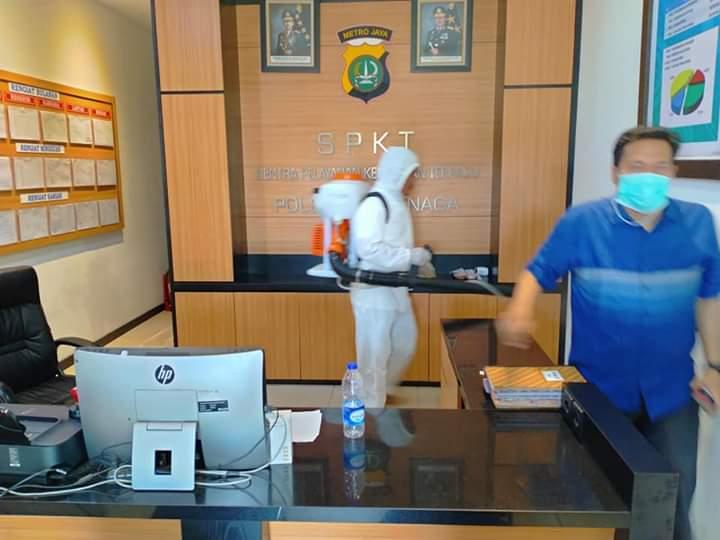 Petugas kesehatan saat melakukan penyemprotan disinfektan di Polsek Teluknaga.