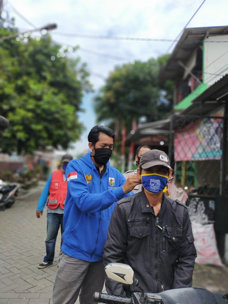 Ketua KNPI Kota Tangerang Uis Adi Dermawan saat memberikan masker kepada warga RT 06/02 di Pinang, Sabtu (11/4/2020).