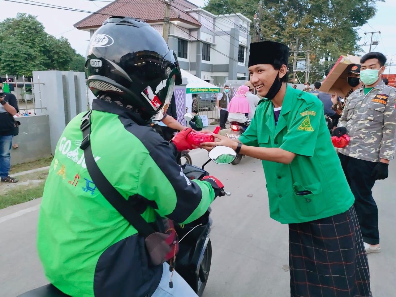 Aksi sosial Gerakan Pemuda Ansor Curug membagikan masker kepada pengendara yang melintas di Jalan PLP Curug, Minggu (3/5/2020).