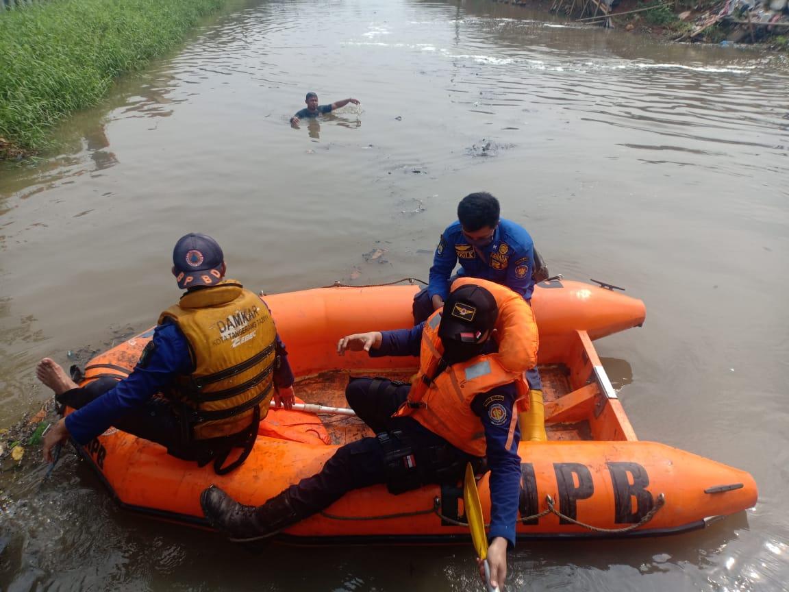 Personel BPBD Kota Tangerang berusaha mencari bocah yang tenggelam di sungai Ledug.
