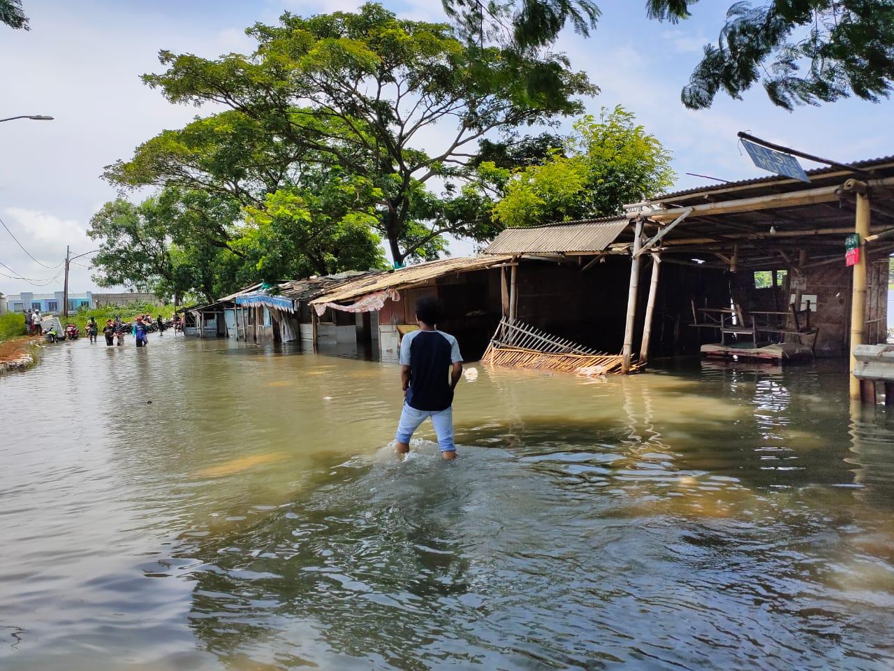 Suasana jalan menuju Perumahan Total Persada di Kelurahan Gembor, Kecamatan Periuk, Kota Tangerang masih terendam banjir, Senin (22/02/2021).