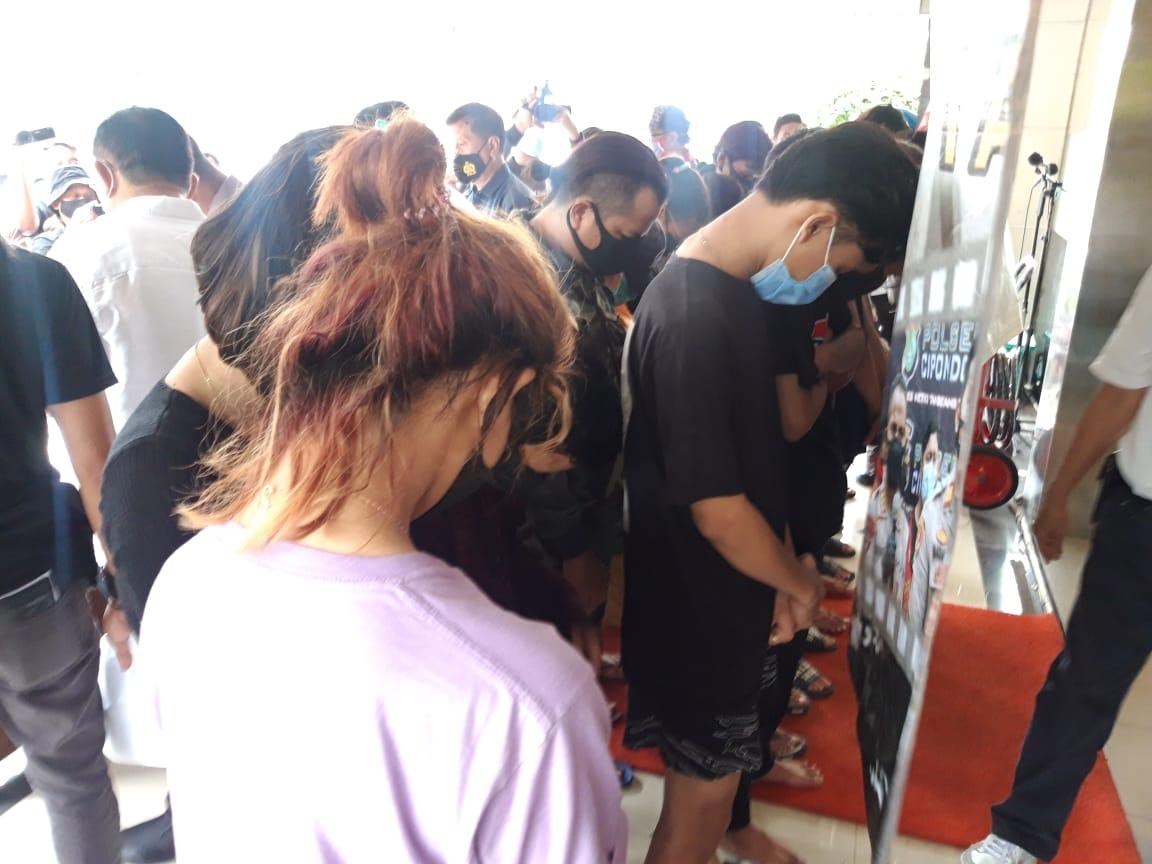 Sejumlah pelaku kasus pesanan perempuan atau open booking order (BO) beserta muncikari atau joki online berbaris menghadap dinding, Kota Tangerang, Senin (8/3/2021).