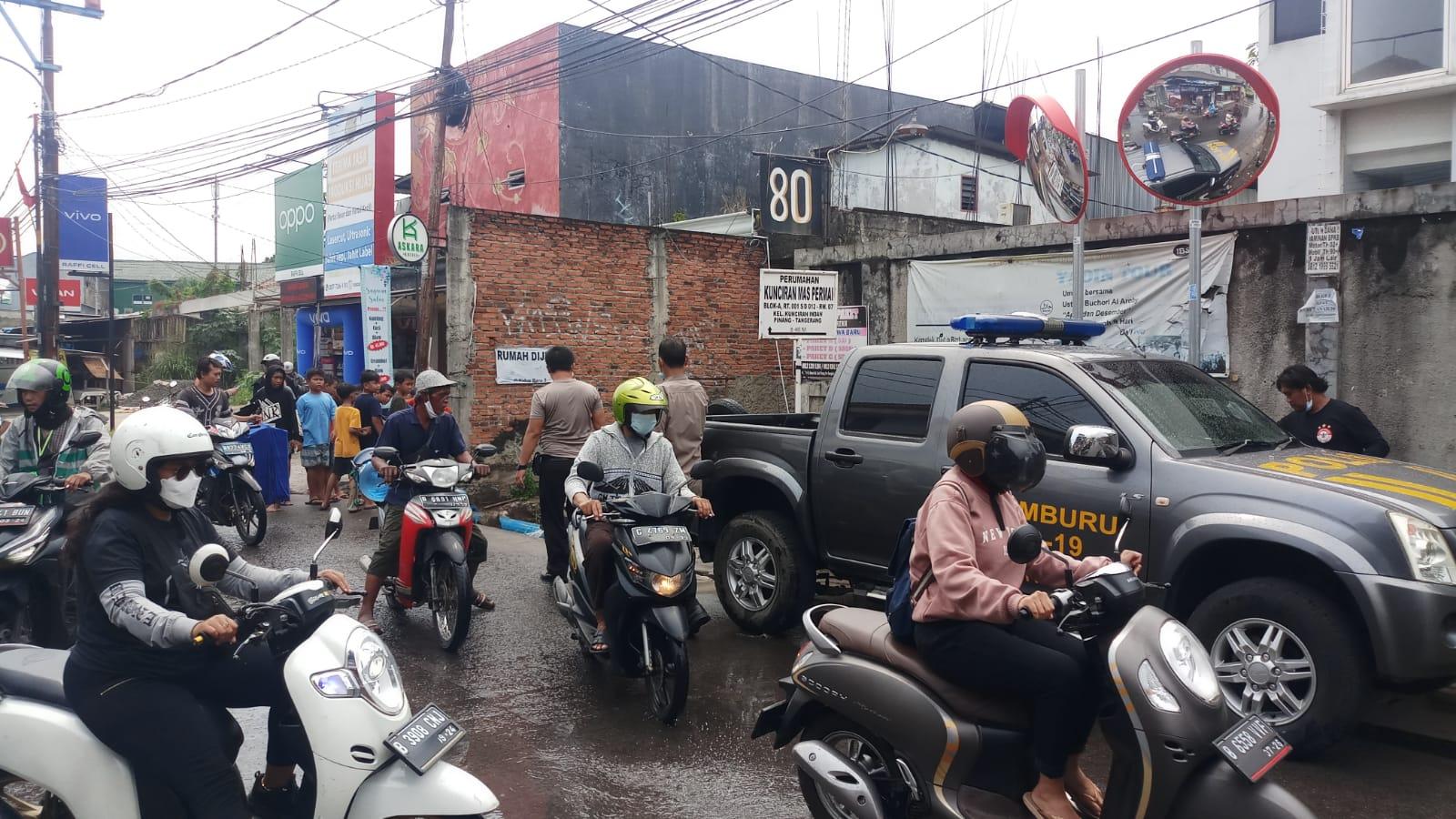 Suasana warga yang memadati insiden satu unit mobil pikap terperosok kedalam saluran air di Jalan Sultan Ageng Tirtayasa, Kelurahan Kunciran Indah, Kecamatan Pinang, Kota Tangerang, Senin 27 September 2021 siang.