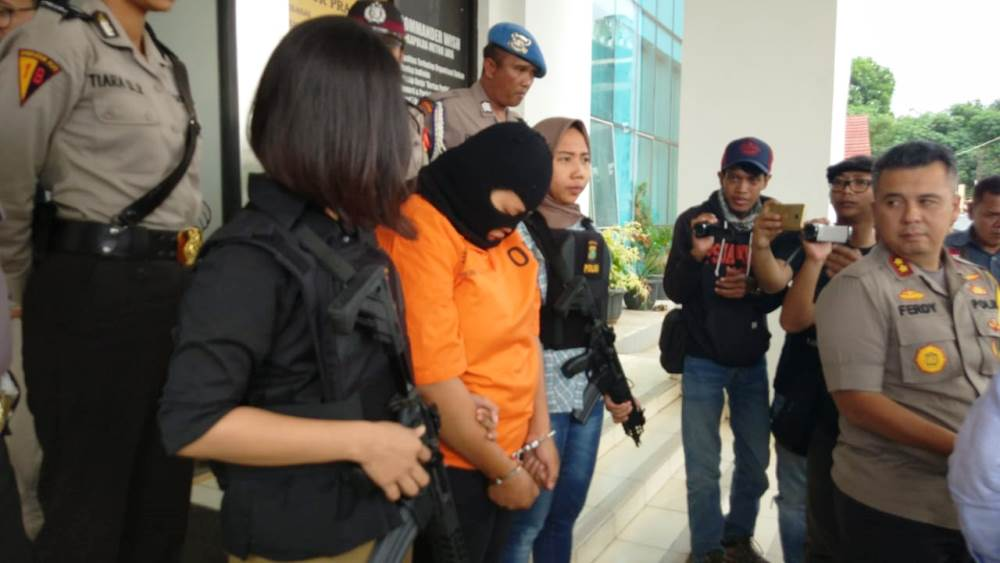 Tersangka Lilis Siti Saadah, 20, (berpakaian oranye) tertunduk menyesali perbuatannya yang tega telah membunuh sang buah hatinya.