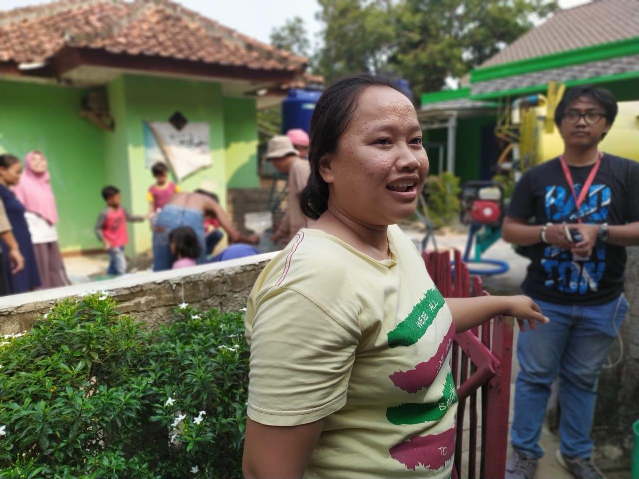Tampak seorang warga bernama Yuli,31 saat menyuci baju di tampungan air dari aliran Kali Cisalak.