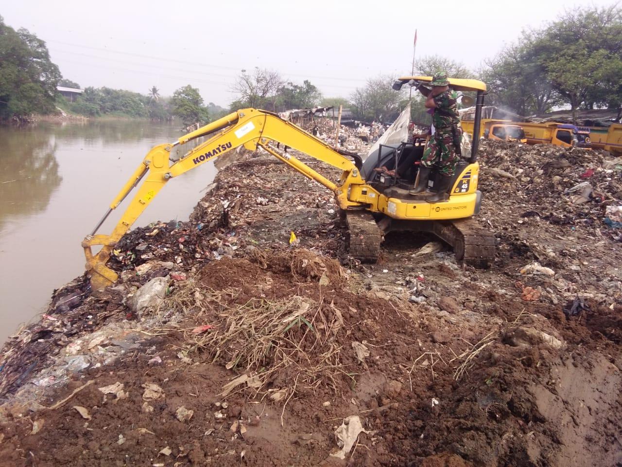 Sampah di Bantaran Sungai Cisadane, Kecamatan Teluk Naga, Kabupaten Tangerang di bersihkan menggunakan alat berat beko dari Dinas Lingkungan Hidup dan Kebersihan (DLHK).