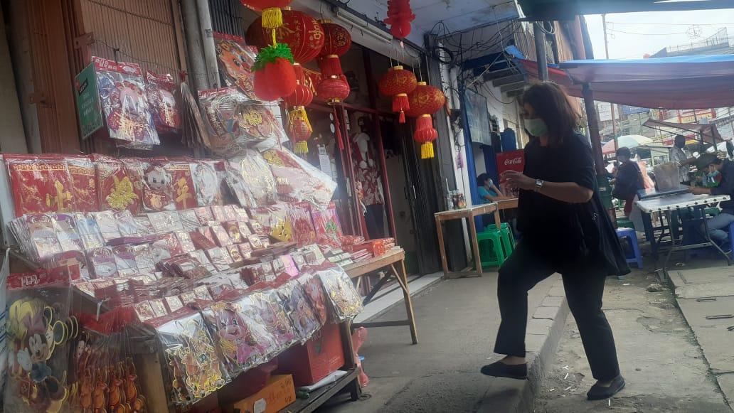 Suasana pedagang pernak-pernik Imlek di kunjungi pembeli di Kawasan Pasar Lama, Jalan Kisamaun, Kota Tangerang, (26/1/2021).