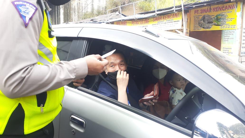 Anggota kepolisian saat memberhentikan satu unit kendaraan pribadi di Pos Penyekatan yang berlokasi di wilayah Bitung, Kabupaten Tangerang, Kamis (6/5/2021).
