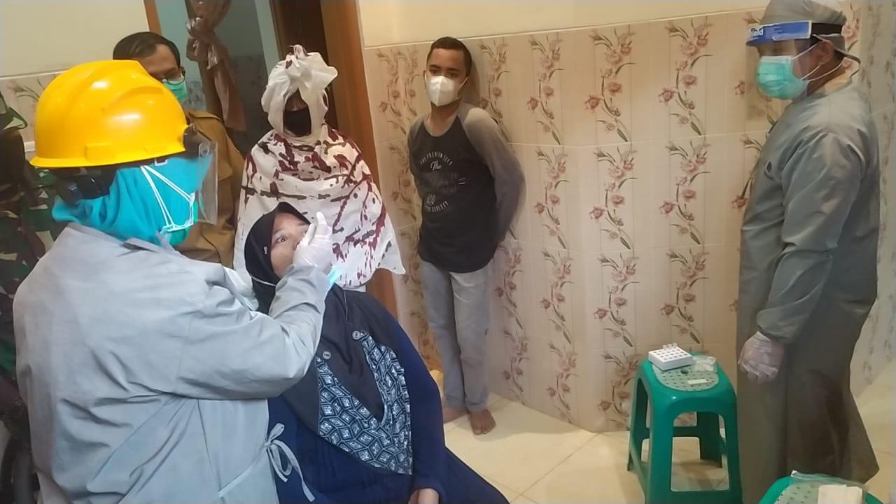 Salah satu warga saat di Tes Antigen guna mencegah penyebaran COVID-19 yang di hadiri sesosok 'pocong' terbungkus kain kafan, terlihat gentayangan di wilayah Kecamatan Setu, Tangerang Selatan, Senin (17/5/2021).