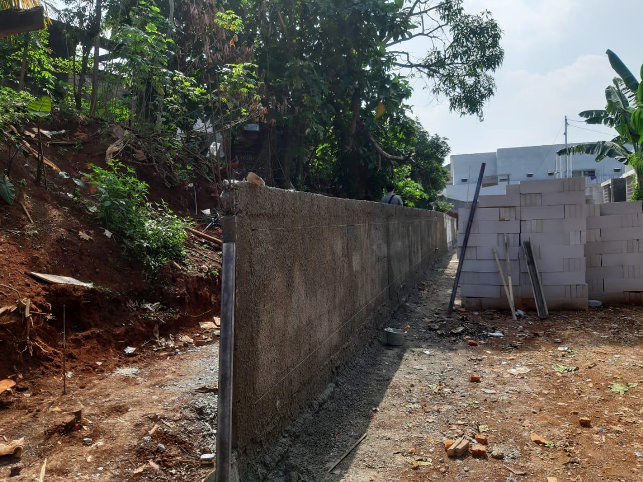 Satu bangunan tembok memisahkan antara Kampung Bulak dan kawasan perumahan Bukit Nusa Indah.